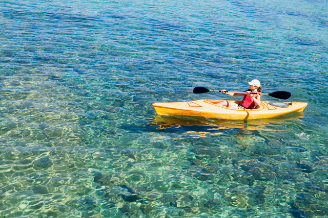 a woman in a yellow kayak on clear, calm water