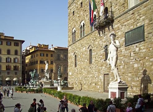 Preciosa imagen de El David de Miguel Ángel Buonarroti a los pies del Palazzo Vecchio (Palacio Viejo) en la Plaza de la Señoría de Florencia, con la estatua ecuestre de Cosme I y la fuente de Neptuno, al fondo