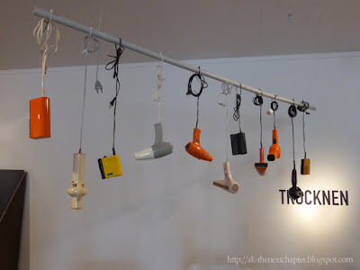 Different hairdriers on a row, hanging from their power coards - a square one in the foreground, then one that looks like a dildo and then variants of classic driers