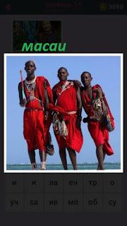 стоит трое мужчин масаи в красной одежде