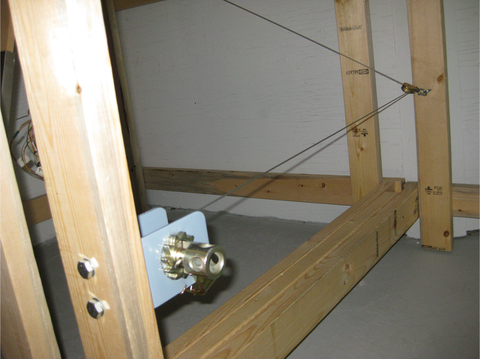 Locking winch with steel aircraft cable bolted to a 2 x 4 wooden support leg on model railroad benchwork