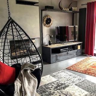 salon avec meuble en métal et fauteuil suspendu