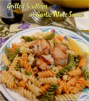 Grilled Scallops in Garlic Wine Sauce. Grilled (or pan seared) sea scallops are served over rotini tossed in a light sauce of wine and broth with garlic and green onions. | Recipe developed by www.BakingInATornado.com | #recipe #grilling