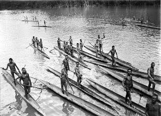 Asmat people with dugout canoes