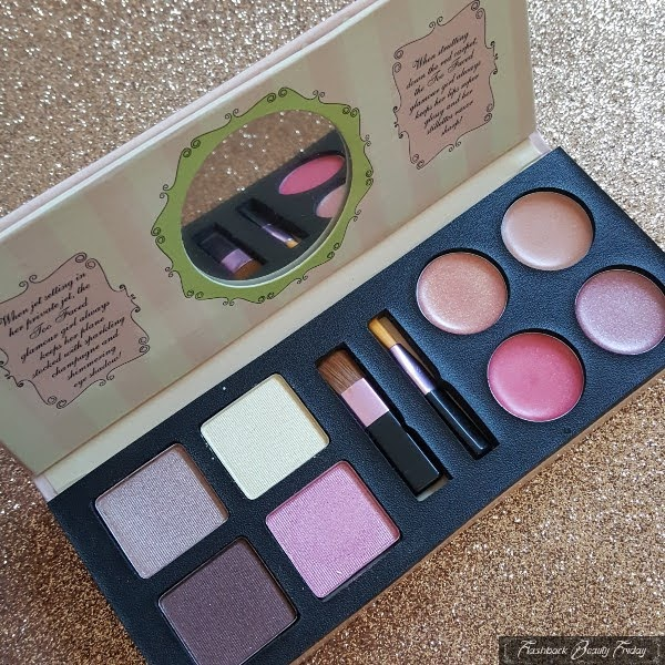 open makeup palette with eye and lip quad on glitter background