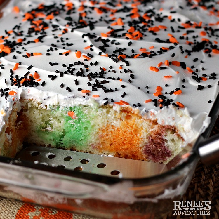 Pan of Halloween Jello Poke Cake by Renee's Kitchen Adventures with a few pieces cut out to show the colors of the gelatin in the cake
