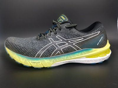 Asics GT-2000 10, lateral view. A black upper with a mixed yellow and white midsole with a streak of a turquise at the top.