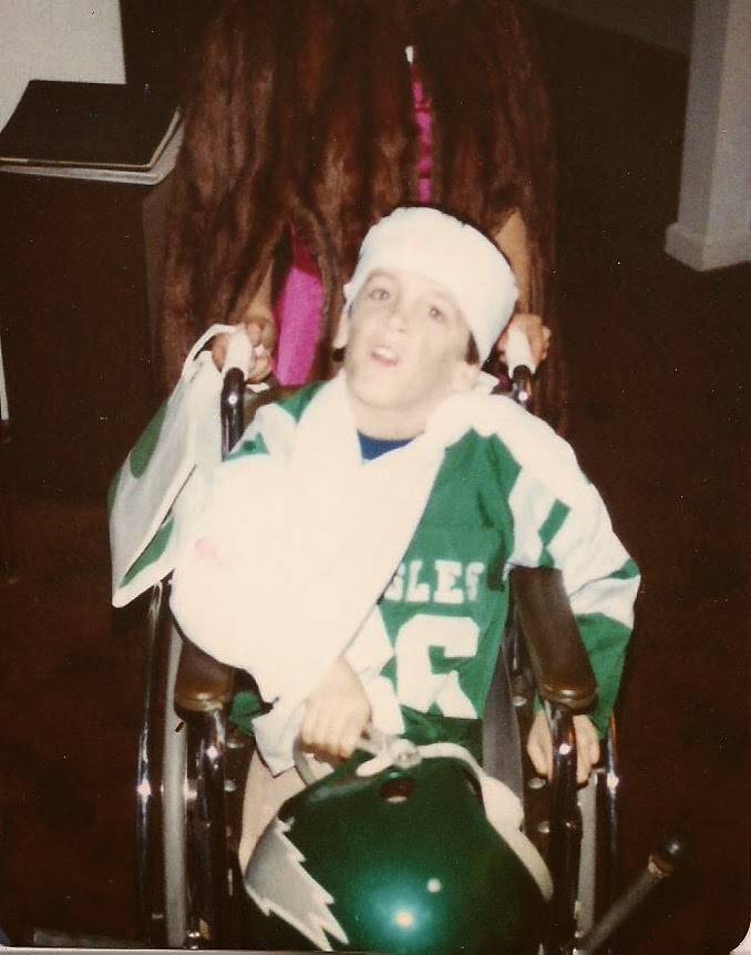 Me, under 10, sitting in a manual wheelchair with an Eagles jersey with bandages on my head and arm in a sling