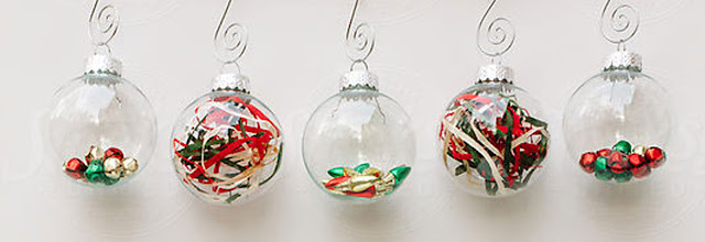 Five clear ornaments filled with red, green and gold doodads.