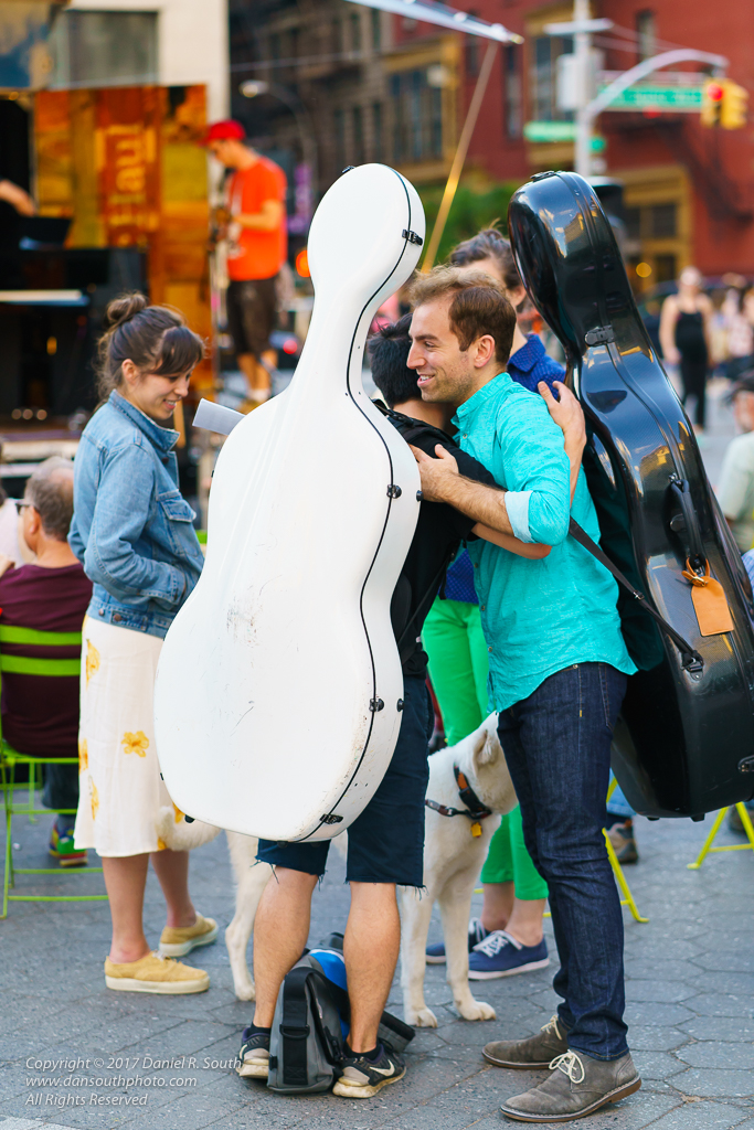 a photo of two cellists embracing in union square park new york