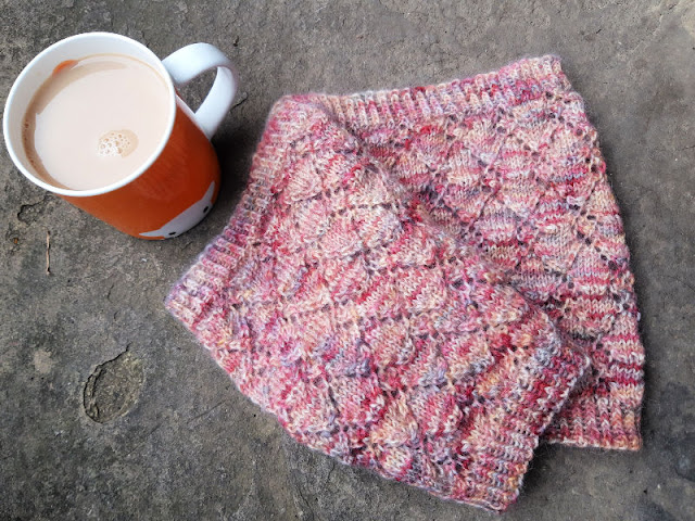 Image shows a knitted cowl with a lace pattern in shades of pink lying on a stone flag next to an orange mug of tea