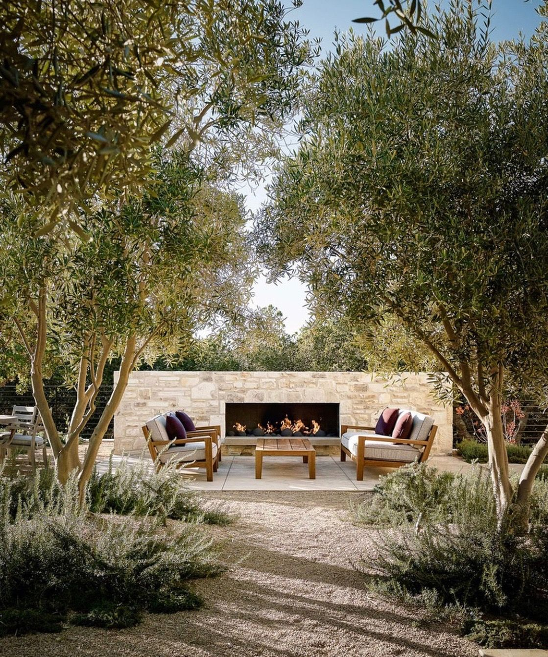 pea stone gravel patio landscape exterior inspiration mediterranean low-maintenance olive trees outdoor stone fireplace pavers