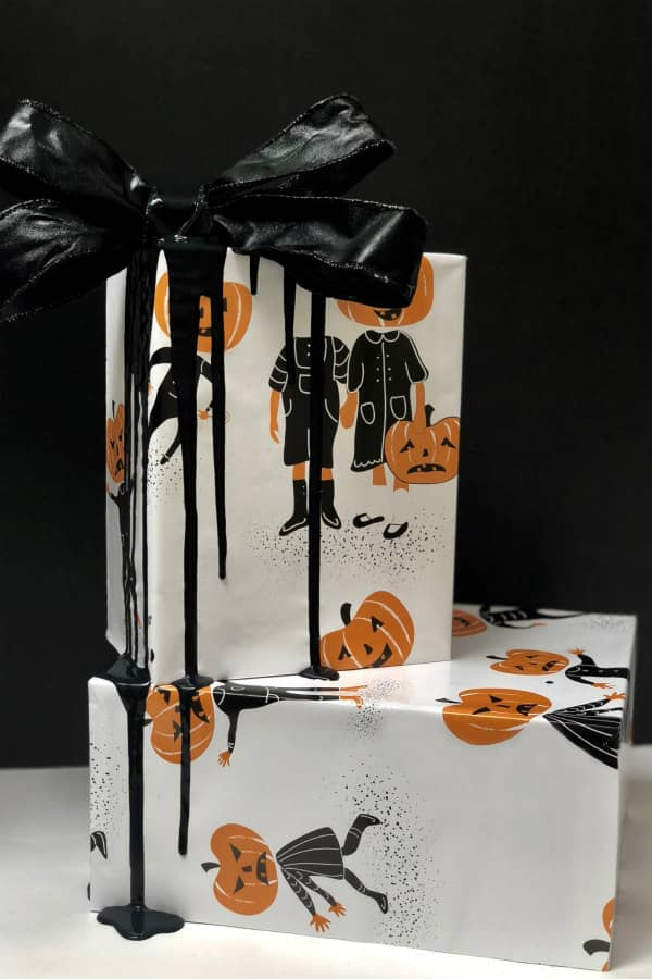 pair of Halloween presents wrapped in pumpkinhead paper with black ribbon and bow
