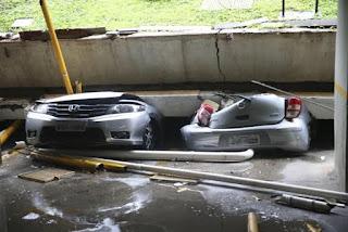 Jardim de prédio desaba sobre garagem e esmaga carros