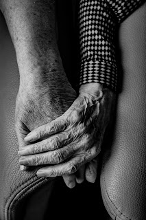 An elderly hand holds onto a younger hand