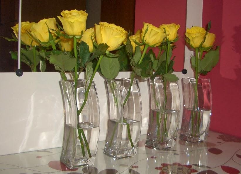 Gelbe Rosen in vier quadratischen Vasen