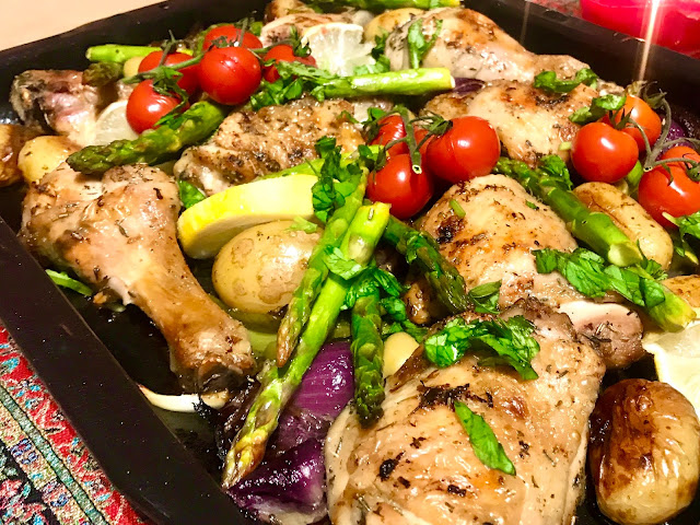 Greek chicken tray bake with asparagus, tomatoes, potatoes and red onion