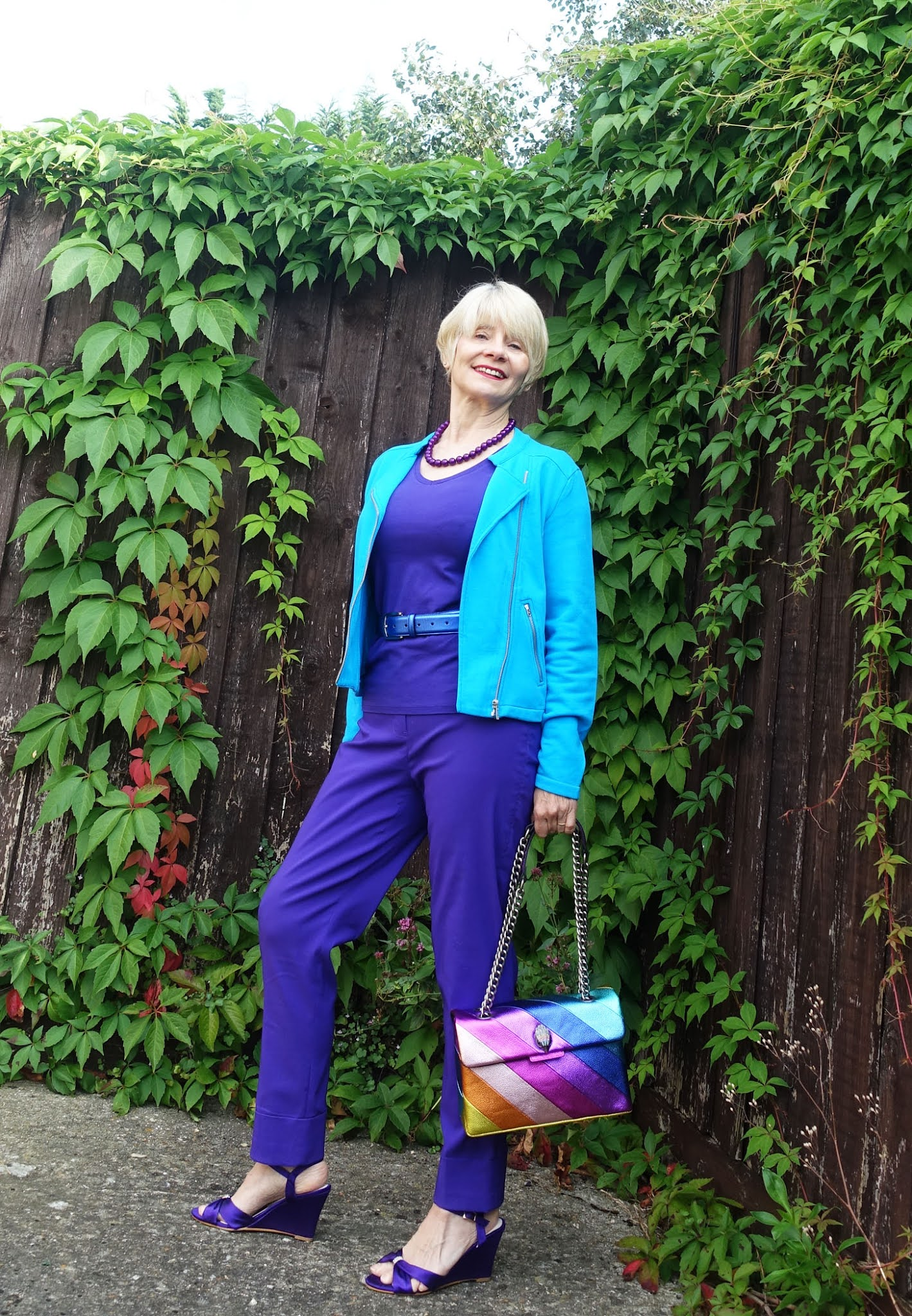 Over 50s style blogger Gail Hanlon in all purple with a bright blue jacket