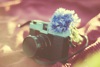 Bleached picture of camera with a blue flower on it