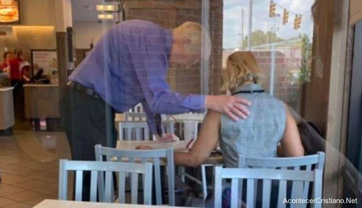 Empleado orando por cliente en restaurante