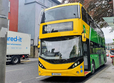 Bus with new Bus Eireann paint job:  yellow front and green back, parked in Eyre Square at the bus stop for route  407 -  Bóthar an Chóiste