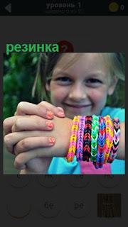 на руках у девочки одеты несколько резинок цветных