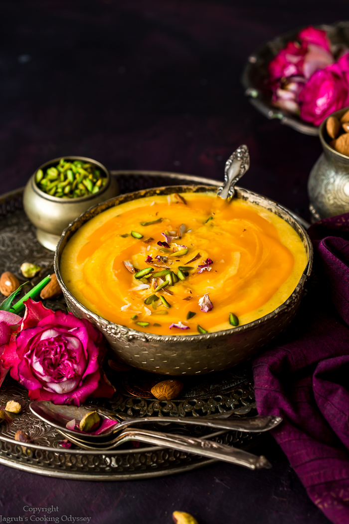 Mango kheer served in a vintage silver bowl garnished with slivered nuts with a spoon.