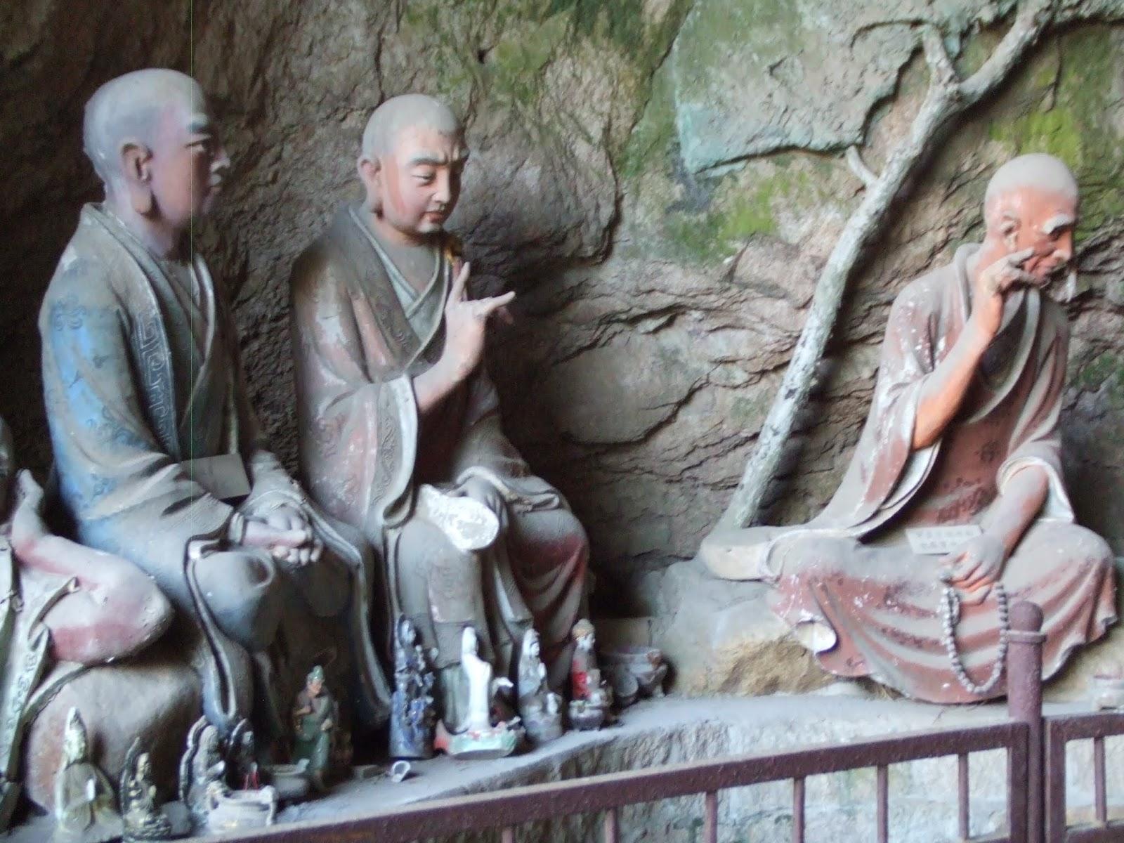Stele mit chinesischen Figuren vor Felswand und roter Zaun