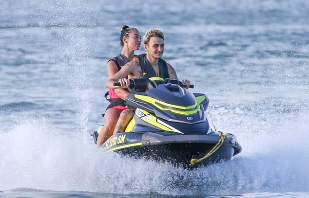 Dua Lipa reveals her pert derriere in high-cut swimsuit before heading on jet ski ride with beau Anwar Hadid in Miami