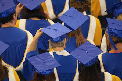 Crowd wearing graduation caps and gowns, viewed from behind