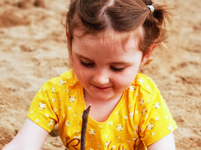 Image of a 3 year old girl building a sandcastle on the beach wearing a wellow floral top and hair in pigtails