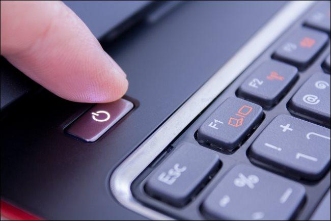 إصبع يضغط على زر تشغيل الكمبيوتر المحمول لإغلاقه.