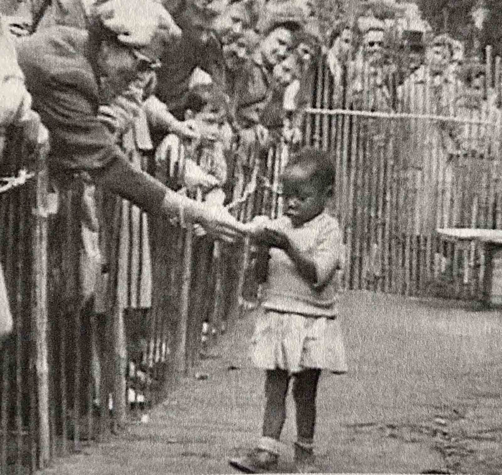An African girl is shown at the 1958 Expo in Brussels, Belgium that featured a 'Congo Village' with visitors watching her from behind wooden fences.