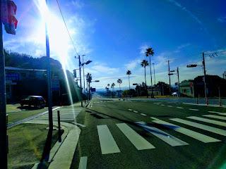 青い空、早朝で車のない幹線道路に差す朝日。