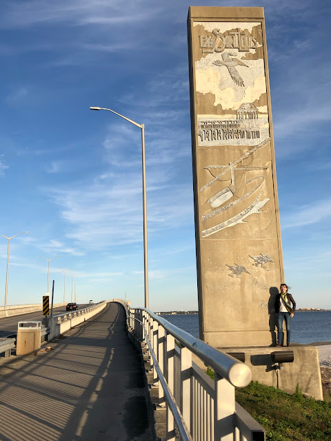 woman standing at end of bridge over bay