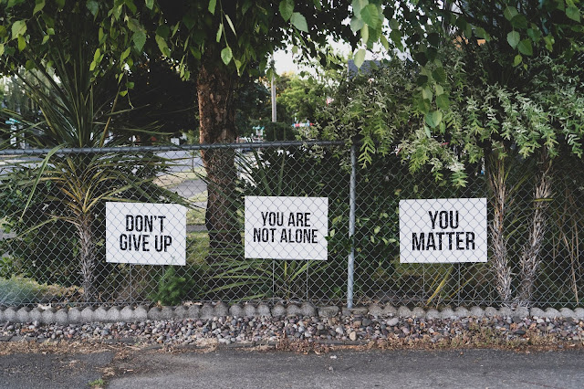 A road with long grills one one side with sign posts saying,'don't give up','you matter','you are not alone'
