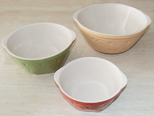 A set of 3 ceramic nesting bowls in in yellow, green and red.