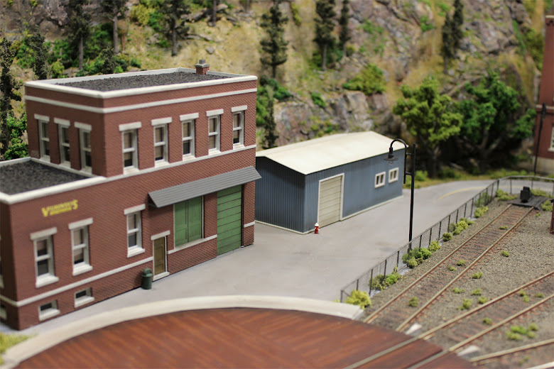 Cutting Scissors Co. kit and scratch built garage across from rail yard and scratch built chain link fence