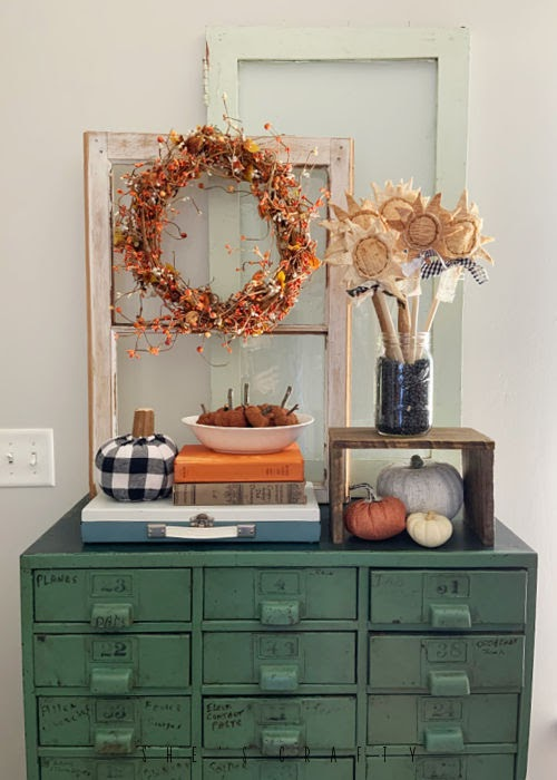 Hardware Cabinet with layered windows, pumpkins and sunflowers.