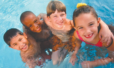 Image of kids in the water hugging and laughing after playing one of my games for swimming lessons, Simon says in the pool.