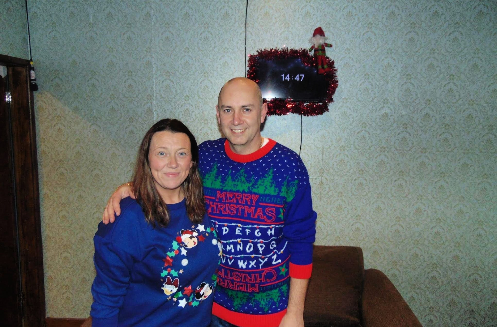 man and woman in christmas jumpers