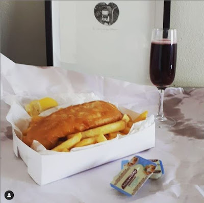 Packet of fish and chips, glass of sparkling shiraz and a framed wood engraving on a table.