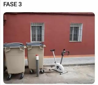 Bicicleta estática junto a cubos de basura