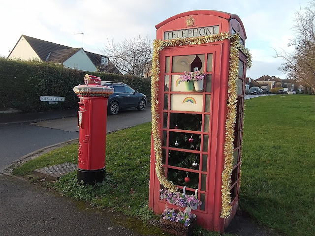 Telephone box with its own Christmas tree and tinsel