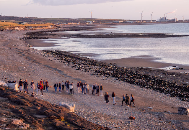 Photo of young people gathering on the beach later on the day their school closed (their faces have been blurred intentionally)