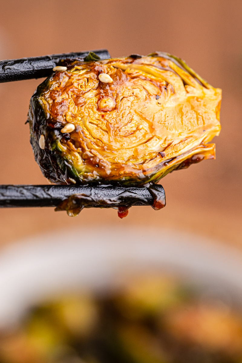 Closeup photo of a Kung Pao Brussels Sprouts being help with chopsticks.