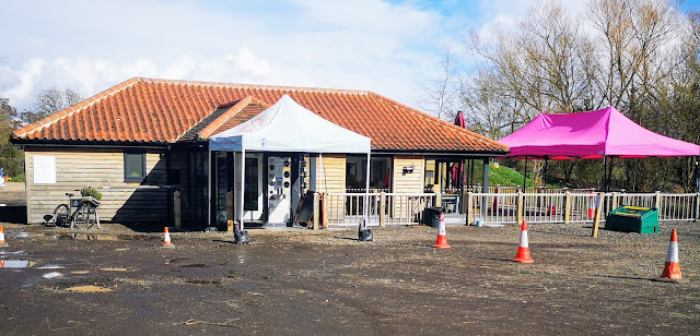 Image shows a single story tearoom and cafe that has an outdoor seating area and has clearly marked covid 19 compliant protocol in place.