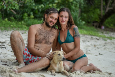 happy couple in the beach with a dog