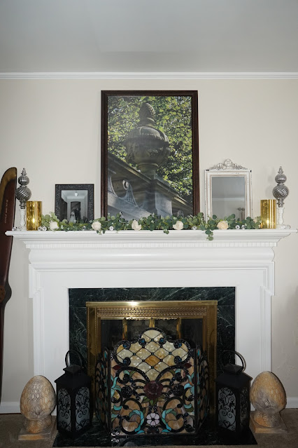 Mantel decorated in a cottage with rose garland and photos
