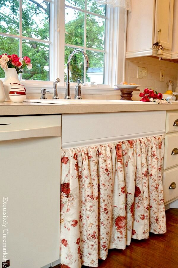 Cottage style floral kitchen sink skirt in off white kitchen with flowers in vases